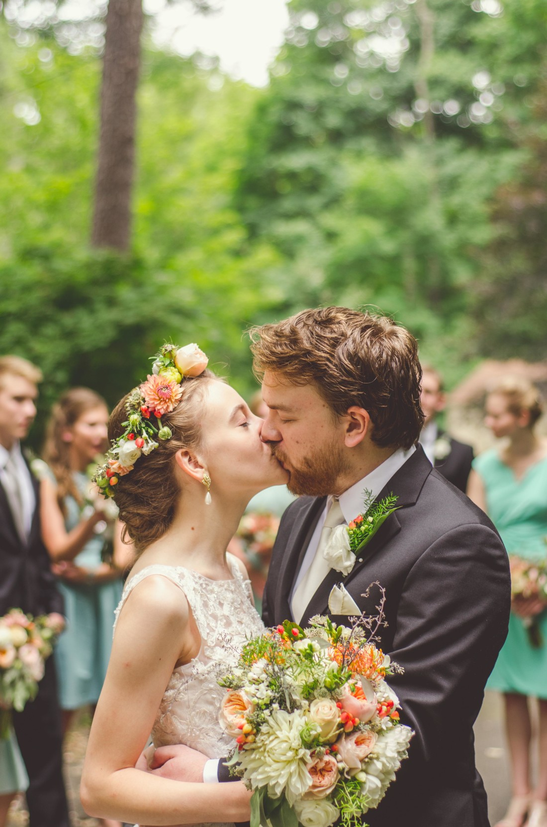 husband and wife kissing with bridal party in the background