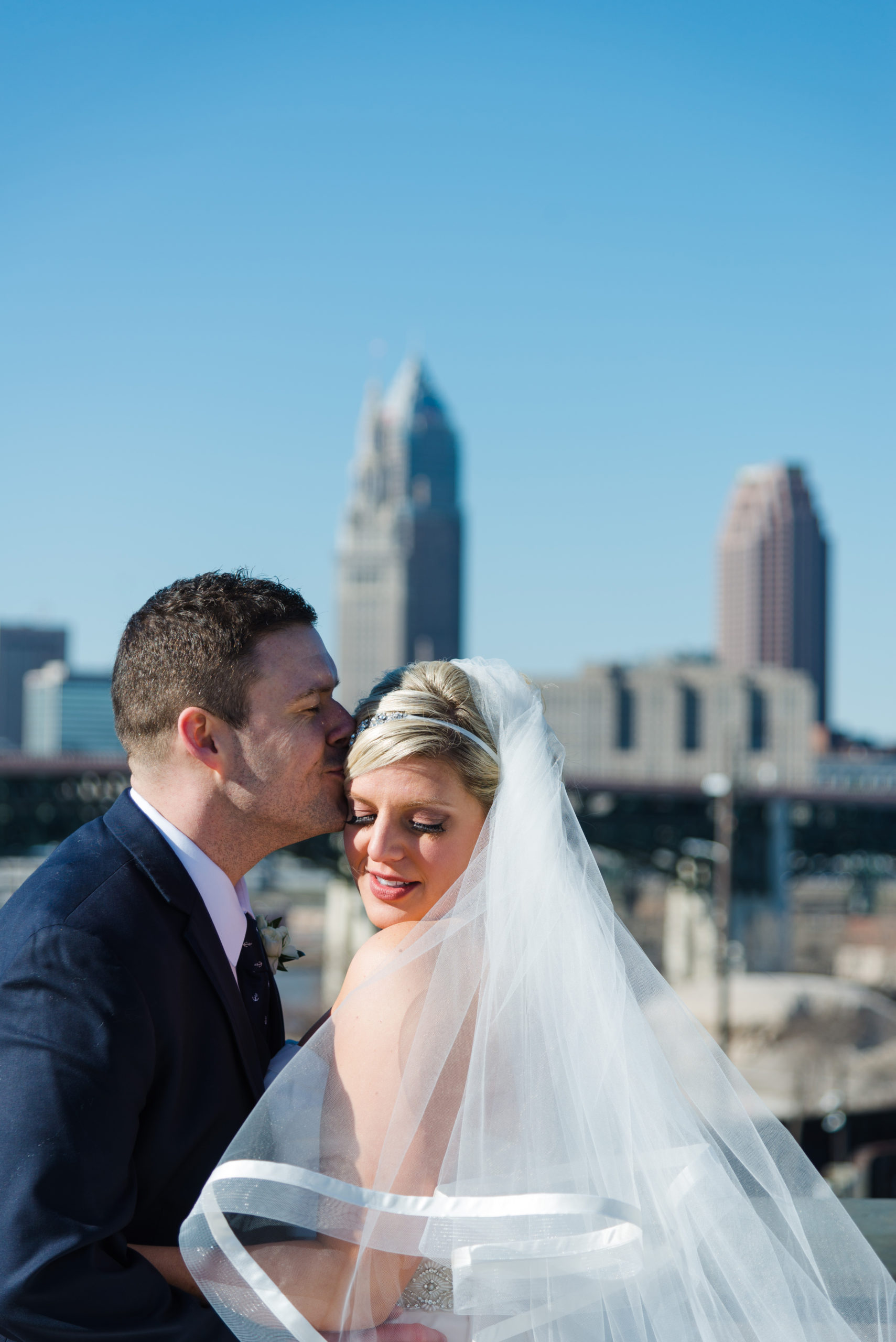 Caucasian man kissing woman on head in front of cleveland skyline