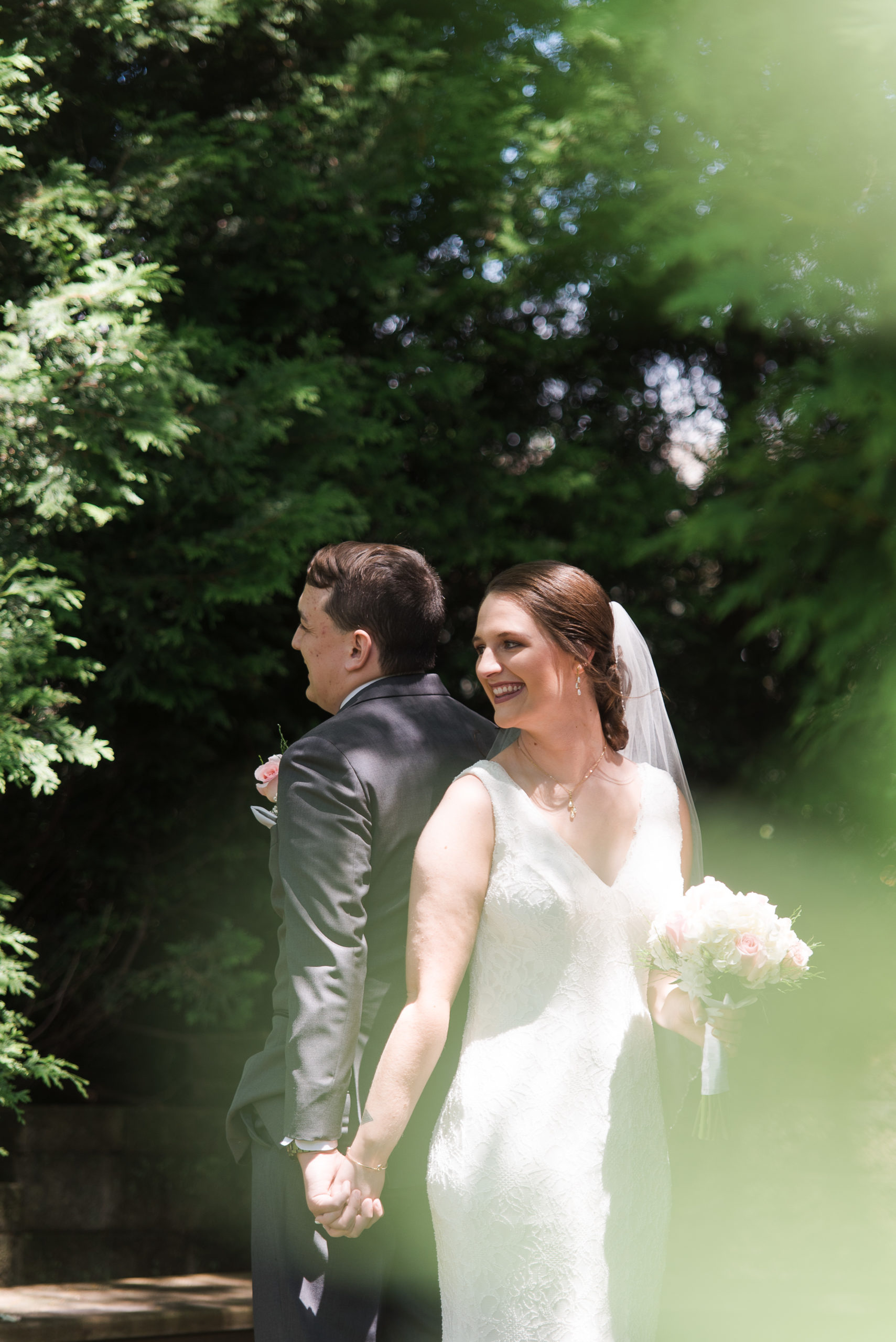 Caucasian male in suit and female in white wedding dress holding hands back to back